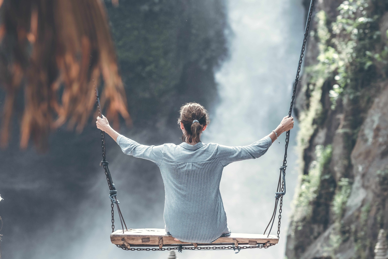 Jeune fille se balançant au dessus d'une chute d'eau